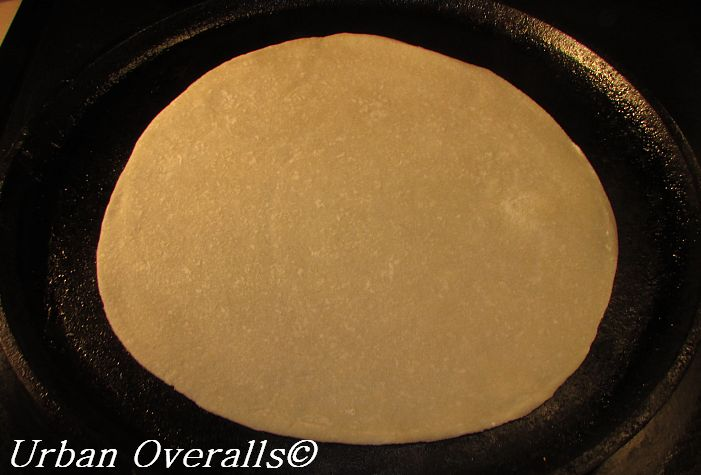 uncooked flour tortilla on the skillet